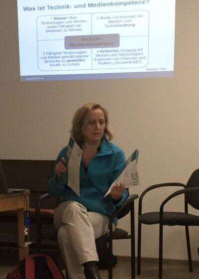 Nicola Röhricht sitzt vor einer Präsentationsleinwand mit Informationen zur Digitalisierung